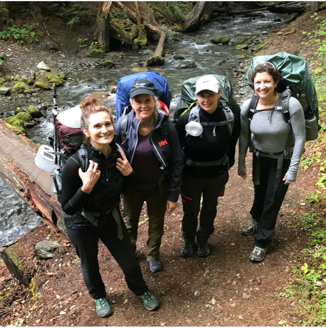 Four women stand in front of a creek crossing, wearing backpacking backpacks.