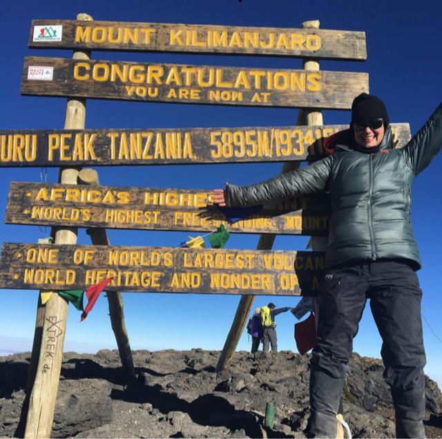 A woman stands in a black puffy and beanie in front of the Kilimanjaro summit sign.