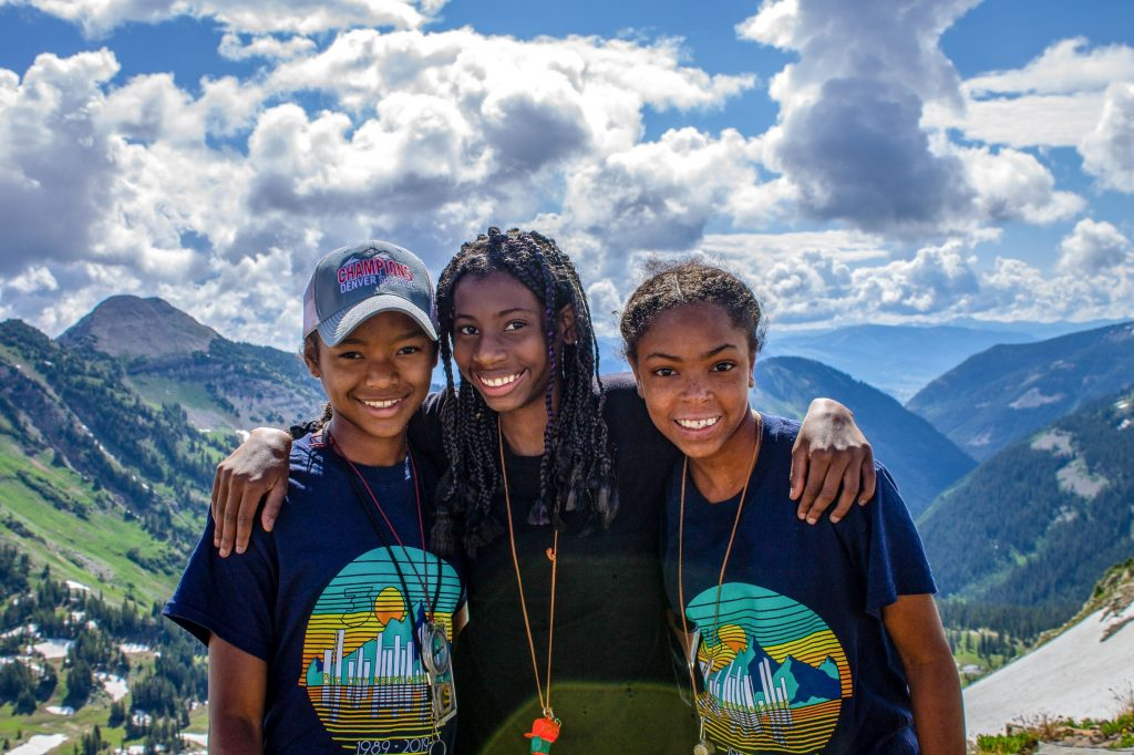 Three young women stand in front of a mountainous backdrop. They have their arms around each other, and are smiling for the camera.