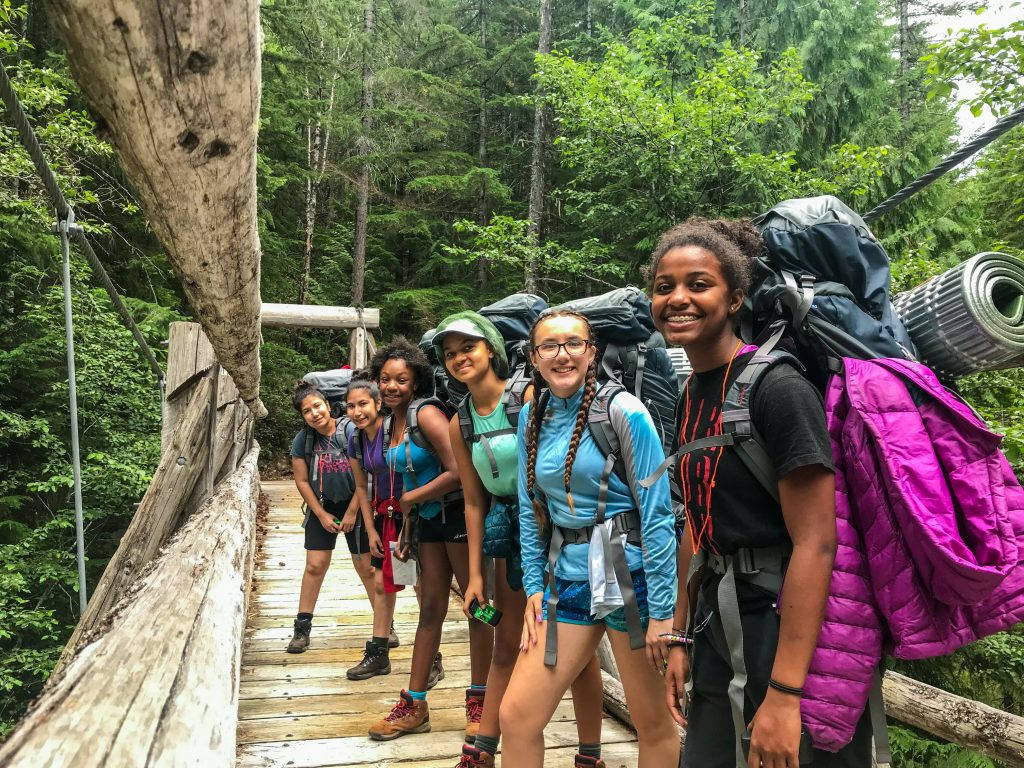 Six youth with backpacking gear stand in an angled line on a wooden bridge. A dense forest stands in the background.