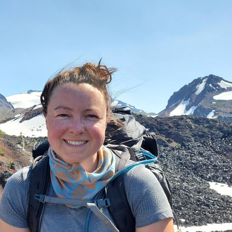 Anne is wearing a backpack and a bluish short sleeved shirt, with a bandanna around her neck, smiling. She is standing on a hiking trail, and one of the Three Sisters is looming in the background.